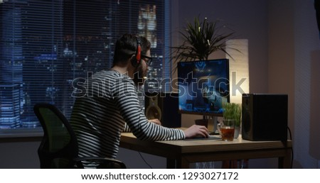 Medium shot of a young man playing shooting video game inside a room #1293027172