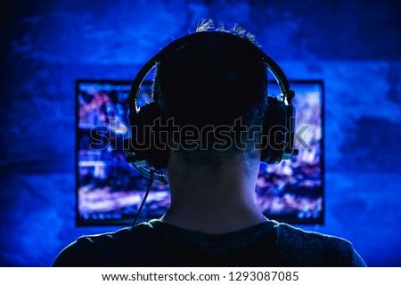 Men wearing headphones playing video games late at night #1293087085