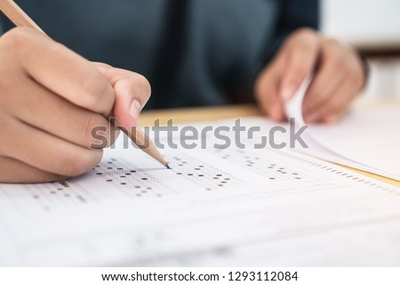 Education test exam concept, high school / university student holding pencil writing paper answer sheet on lecture chair for taking exams in examination room or classroom. Educational assessment ideas #1293112084