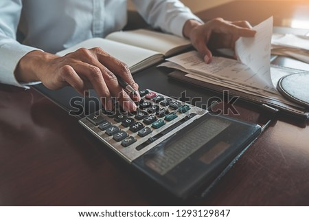 Woman with bills and calculator. Woman using calculator to calculate bills at the table in office. Calculation of costs. #1293129847