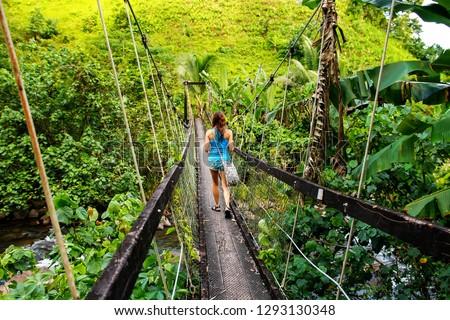 Young woman walking on suspension bridge over Wainibau stream, Lavena Coastal Walk, Taveuni Island, Fiji. Taveuni is the third largest island in Fiji. #1293130348