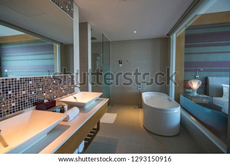 Interior decoration, design for family bathroom which has a bath, wash basin, toilet and tiled wall and floor. Modern bathroom interior with lighting, white toilet, sink and bathtub. #1293150916