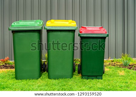 Australian home rubbish bins set provided by local council on back yard in Australian suburb #1293159520