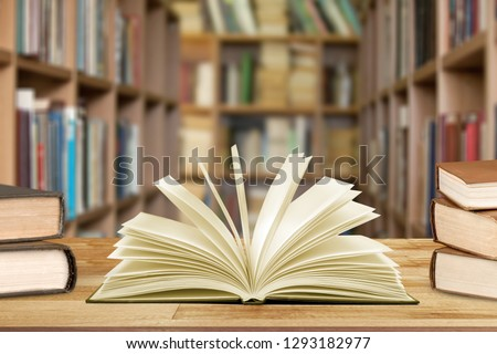 Book in library with old open textbook, stack piles of literature text archive on reading desk, and aisle of bookshelves in school study class room background for academic education learning concept #1293182977