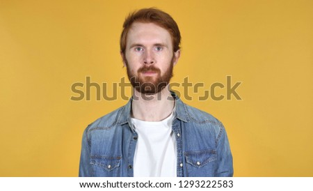 Redhead Man Looking at Camera Isolated on Yellow Background #1293222583