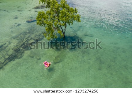 DRONE shot- happy woman enjoying beach holidays on tropical Island relaxing on inflatable flamingo floating on pristine clear sea. People vacations exoticism concept  #1293274258
