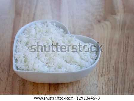 Steam rice in white bowl  heart shape on wooden table, Home made cooking jasmine rice on table #1293344593
