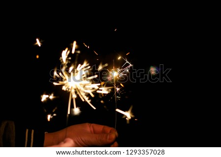 Abstract sparklers background bright festive Christmas and happy new year the man hold hand sparkler motion blurred in wind at winter dark night for celebration and hope background.Vivid black tone. #1293357028