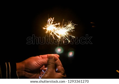 Abstract sparklers background bright festive Christmas and happy new year the man hold hand sparkler motion blurred in wind at winter dark night for celebration and hope background.Vivid black tone. #1293361270