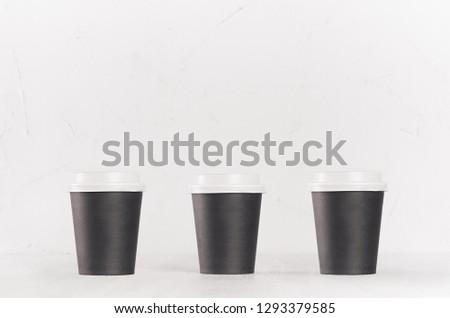 Coffee mockup - set of three small blank black paper cups with white cap on white wood table, coffee shop interior. Modern elegant concept for branding identity, advertising, design. #1293379585