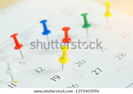 mark the event day with a pin. Thumbtack in calendar concept for busy timeline organize schedule,appointment meeting reminder. planning business meeting or travel holiday planning concept. soft focus #1293403096