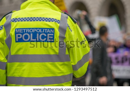 London, UK. 12th January 2019. Metropolitan Police sign on the back of a high visibility jacket worn by police officers escorting & monitoring a street demonstration through central London, UK. #1293497512