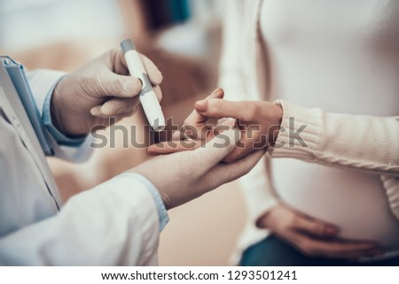 Indian doctor in white gown seeing patients in office. Doctor is measuring blood sugar of pregnant woman with daughter. #1293501241