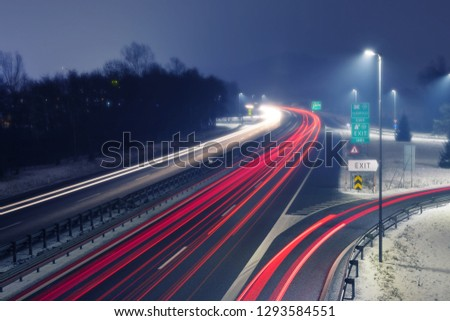 Highway at foggy night with bright trails of light from incoming and outgoing traffic. Transportation, traffic, urbanism and infrastructure concepts. #1293584551