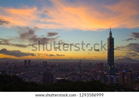 Taipei, Taiwan - September 10, 2008: Sunset moments, golden clouds and blue sky, the lights of urban buildings are sparse. #1293586999