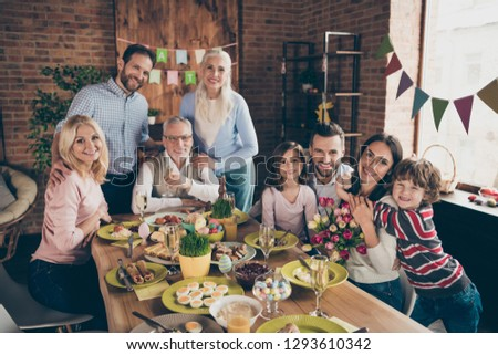 Close up photo of large company gathered family holiday sitting with flowers tulips champagne hugs toothy smiles easter eggs gladness decorations weekend vacation #1293610342