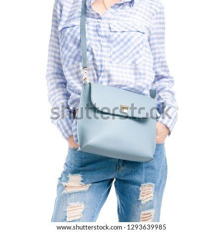 Woman in jeans and blue shirt blue bag in hand macro on white background isolation #1293639985