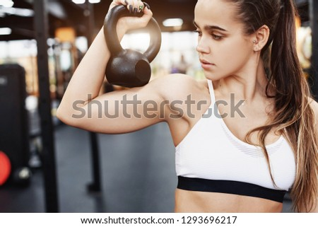 Portrait of a young fit sexy girl with kettlebell posing in the gym. The concept of love for sports and heavy physical loads for building muscle #1293696217