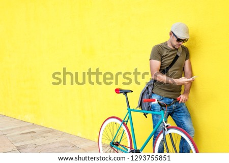 Side view of a young man with a vintage bike and wearing casual clothes and sunglasses standing against a yellow wall while using a mobile phone in a sunny day #1293755851