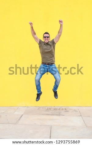 Front view of a young happy man wearing sunglasses jumping against a yellow bright wall in a sunny day #1293755869