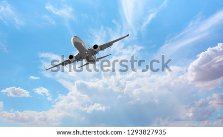 White passenger airplane over the clouds  - Travel by air transport Royalty-Free Stock Photo #1293827935