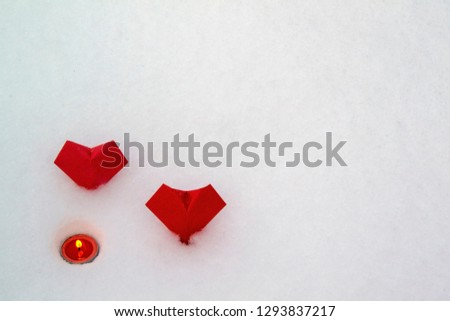 Two paper red hearts (origami) and a burning candle on the background of fresh snow. Valentine's Day. #1293837217