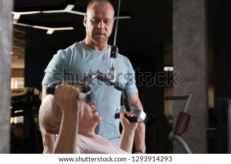 A strong male professional trainer helps his client to a middle-aged woman to correctly perform an exercise on the simulator. The concept of physical activity and health #1293914293