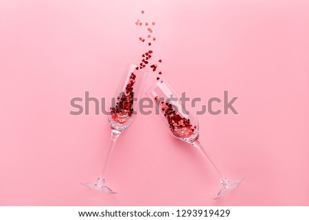 Two clinking champagne glasses with splash of red heart shaped confetti over pink background. Overhead view, copy space. Valentine's Day concept #1293919429