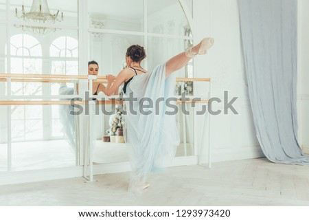 Young classical ballet dancer woman in dance class. Beautiful graceful ballerina practice ballet positions in blue tutu skirt near large mirror in white light hall #1293973420
