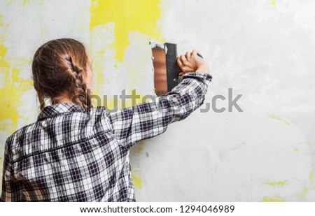 young teenager brunette girl with long hair applying white putty on a wall and smearing by putty knife in a room of renovating house in daytime #1294046989