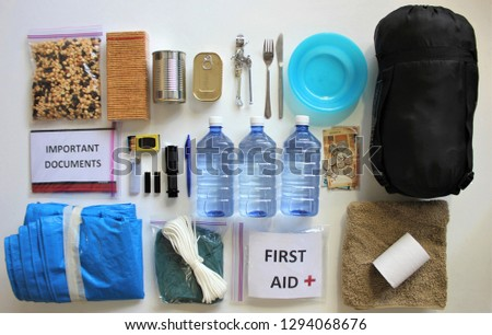 A disaster supply kit,or go bag is a collection of basic items your household may need in the event of an emergency.This survival kit includes first aid items,food,water,flashlight,and batteries. #1294068676