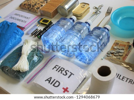 A disaster supply kit,or go bag is a collection of basic items your household may need in the event of an emergency.This survival kit includes first aid items,food,water,flashlight,and batteries. #1294068679