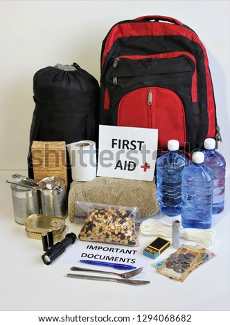 A disaster supply kit,or go bag is a collection of basic items your household may need in the event of an emergency.This survival kit includes first aid items,food,water,flashlight,and batteries. #1294068682