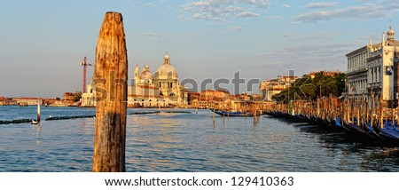 View to the gondolas and boats berth  in Venice. Sunny day. #129410363