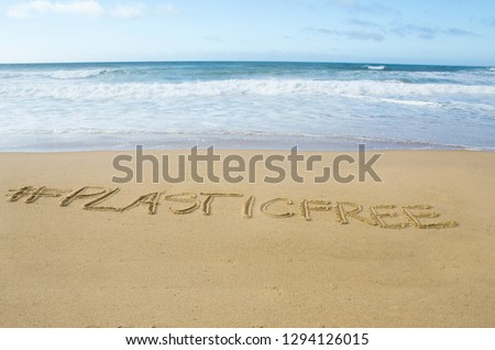 inscription #plasticfree written on the sand on the shores of the atlantic ocean Royalty-Free Stock Photo #1294126015