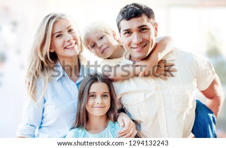 Beautiful smiling family sitting at sofa on background #1294132243