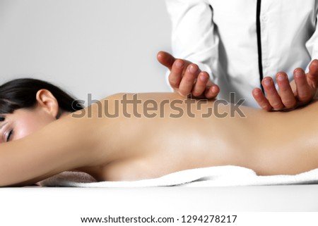 Pleasure of manipulation Ayurvedic massage therapist working on the back of a greasy woman with scented and warm oil. Alternative,ayurveda,masseur,body,business,card,closeup,concept,energy, spa,relax.