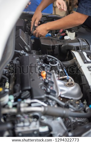 Car service by an auto mechanic in garage, fixing a car battery with wrench, also checking some parts of the engine showing by selective focus. #1294322773