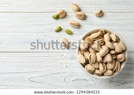 Organic pistachio nuts in bowl on wooden table, top view. Space for text #1294384231