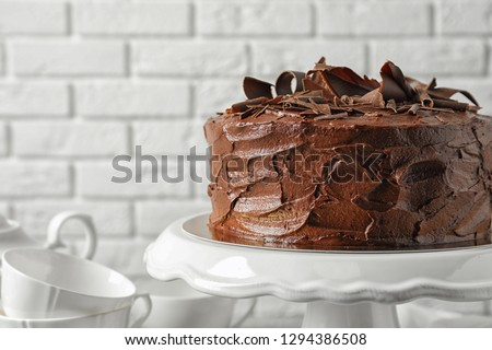 Stand with tasty homemade chocolate cake near white brick wall #1294386508