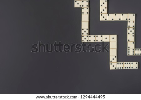 bright domino lay on dark background in line isolated #1294444495