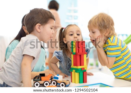 Little kids build wooden toys at home or daycare. Emotional kids playing with color blocks. Educational toys for preschool and kindergarten children. #1294502104