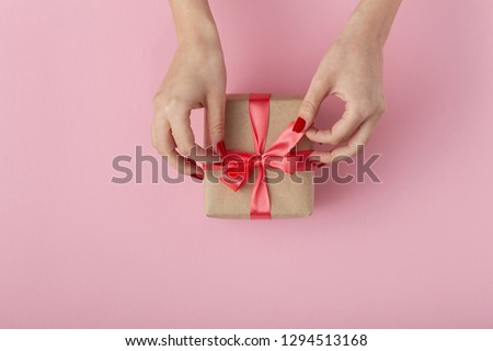 girl unties a ribbon bow on a gift box with hands, female with present wrapped in decorative paper on pink background, top view, concept holiday #1294513168