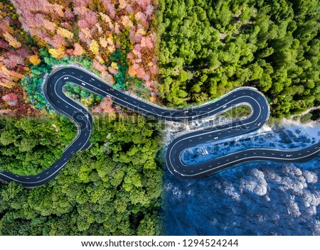 Winding road in all four seasons. Aerial view of a curved highway trough the forest. Composite drone roadway weather image of a hairpin turn Royalty-Free Stock Photo #1294524244