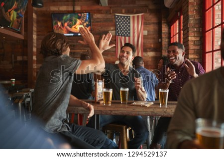 Group Of Male Friends Celebrating Whilst Watching Game On Screen In Sports Bar #1294529137