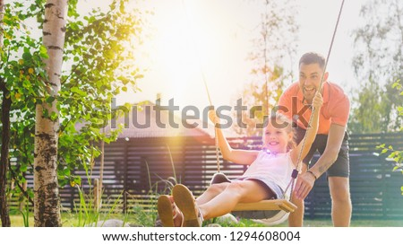 Joyous Father Pushes Swings with His Cute Little Daughter on Them. Happy Family Spends Time Together one Sunny Summer Day in the Idyllics Backyard. #1294608004