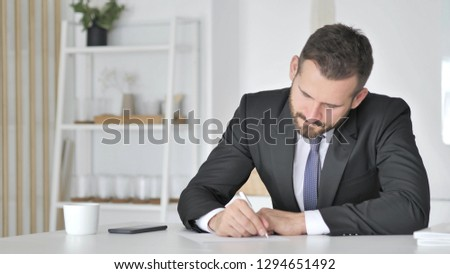 Businessman Writting Documents in Office #1294651492