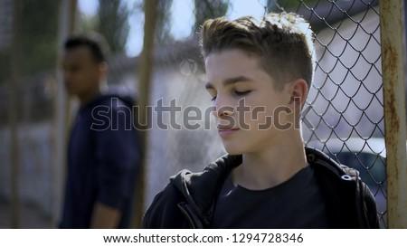 Teenage boys leaning on metal fence, juvenile detention center, orphanage #1294728346