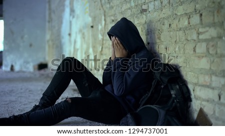Miserable teenager crying in abandoned house, life destroyed by war, sorrow #1294737001