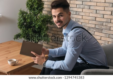 Stylish handsome man reading book at home #1294745383